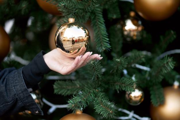 크리스마스 트리에 황금 빛나는 공을 들고 여자의 손보기를 닫습니다.
