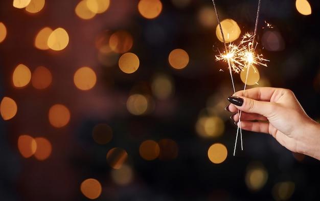 Крупным планом вид женской руки с бенгальским огнем в помещении на рождественские праздники.