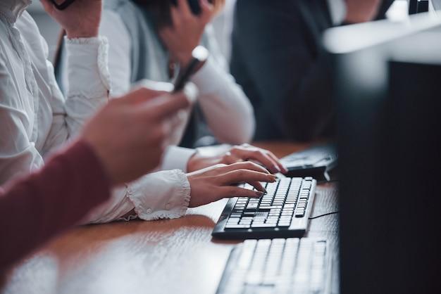 Крупным планом вид женских рук, набрав на клавиатуре. молодые люди, работающие в колл-центре. грядут новые сделки