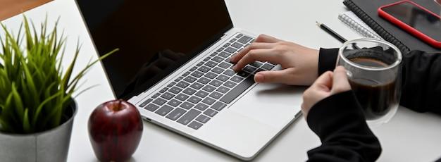 Взгляд конца-вверх женщины печатая на портативном компьютере пока выпивающ чашку кофе
