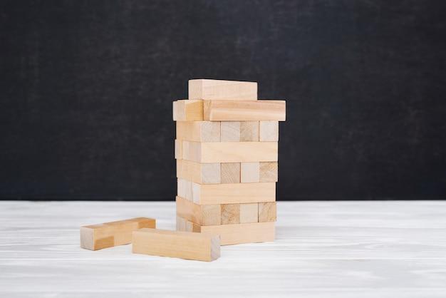 나무 블록 타워의 클로즈업 보기입니다. 취약한 상황에 대한 은유. 도색되지 않은 벽돌에 선택적 초점입니다. 위험 및 계획 전략 개념입니다. 젠가 게임