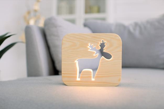 灰色のモダンなソファの上に、スタイリッシュな明るい家のリビングルームのインテリアで、鹿の絵と木製の常夜灯のクローズアップビュー。