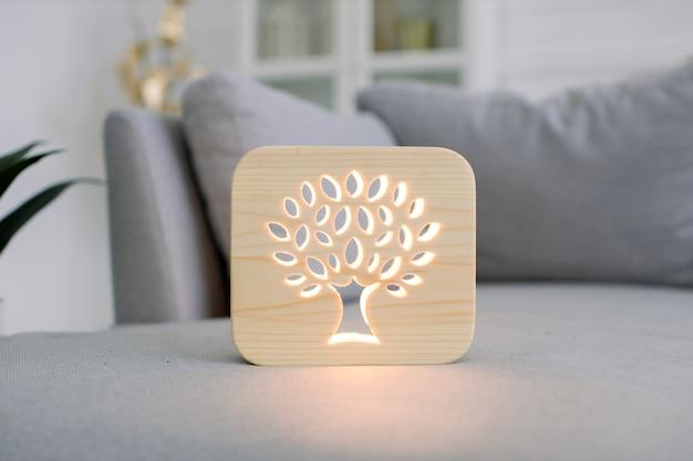 Крупным планом вид деревянной ночной лампы с изображением дерева в стильном светлом домашнем интерьере гостиной на сером современном диване