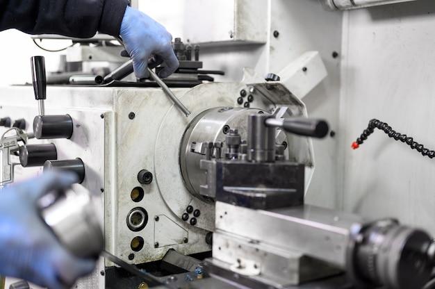 Крупным планом вид рабочего, выполняющего высокоточную токарную операцию на многоосном токарном станке с чпу