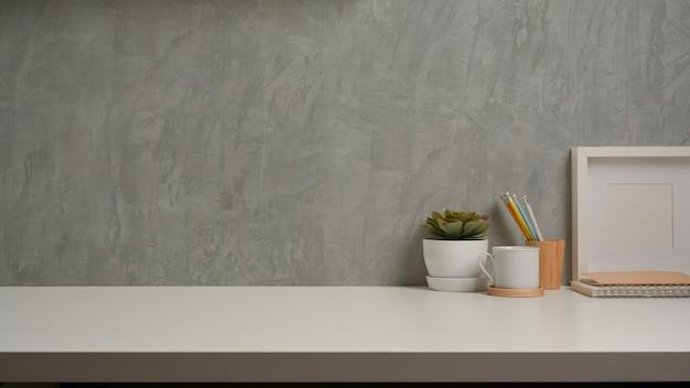 로프트 벽 배경으로 흰색 테이블에 장식 및 복사 공간이있는 작업 공간보기를 닫습니다.