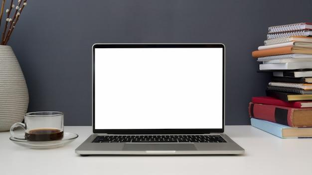 開いている空白の画面のノートパソコン、コーヒーカップ、灰色の壁と白いテーブルの上の本とワークスペースのビューを閉じる