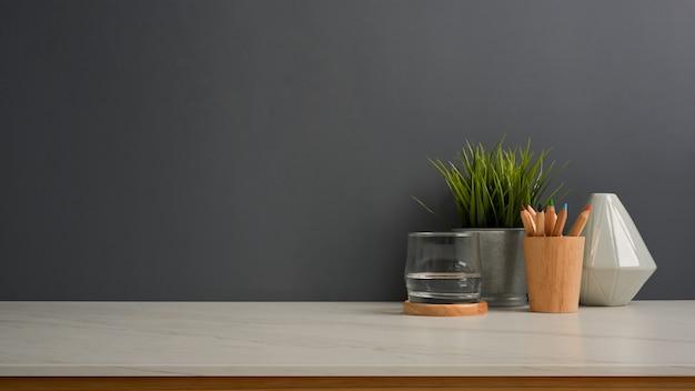 물, 편지지, 꽃병, 식물 냄비의 유리와 홈 오피스의 복사 공간으로 작업대의 뷰를 닫습니다