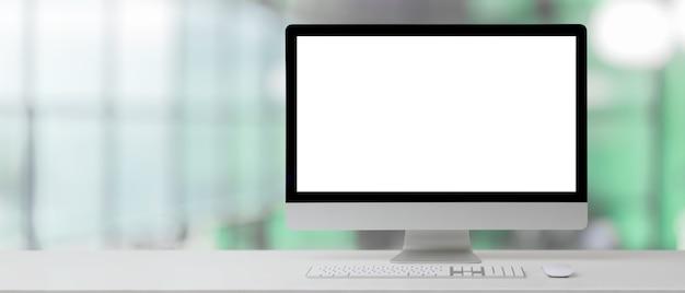 Крупным планом вид рабочего стола с компьютером и копией пространства в размытой офисной комнате