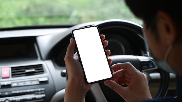보호 마스크를 쓰고 차에 앉아 휴대전화를 사용하는 젊은 아시아 남성의 모습을 가까이서 보세요.