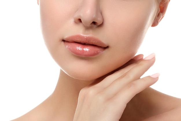 Закройте вверх по взгляду молодой красивой кавказской женщины касаясь ее изолированного лица. контур губ, спа терапия, уход за кожей, косметология