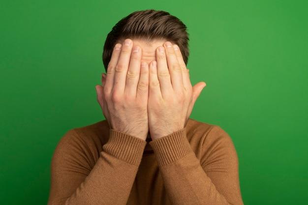 緑の壁に分離された手で顔を覆っている若い金髪ハンサムな男の拡大図