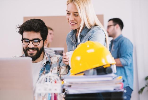 オフィスの机の上のヘルメットと一緒にオブジェクトを見て若い陽気な幸せなカップルエンジニアのクローズアップ表示。