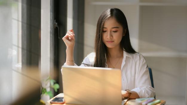 ノートパソコンで彼女の割り当てに焦点を当てた若い大学生のクローズアップ表示