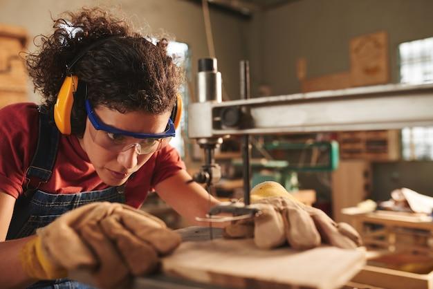 安全メガネと耳守りで若い集中女性大工のクローズアップビュードリルプレスで木の板に穴をあける