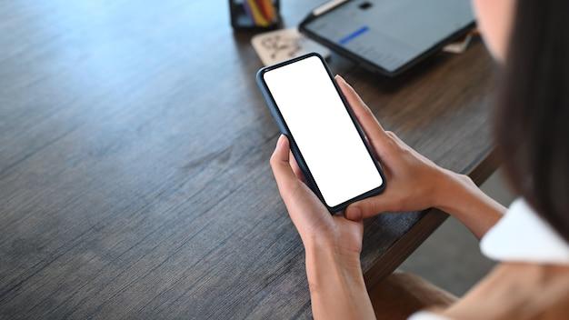 Крупным планом вид молодой девушки-дизайнера, держащей мобильный телефон