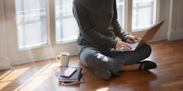 Взгляд конца-вверх молодого женского фрилансера печатая на портативном компьютере пока сидящ рядом с окнами