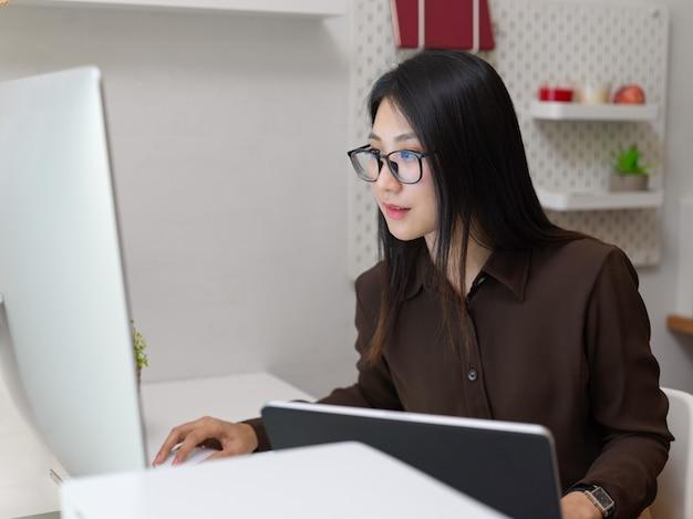 사무실 방에서 컴퓨터 장치로 그녀의 작업에 집중하는 젊은 여성 회사원의 뷰를 닫습니다