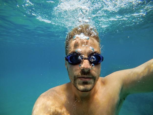 エキゾチックなターコイズブルーの海でダイビンググーグルで若いハンサムなひげを生やした男のクローズアップ表示。