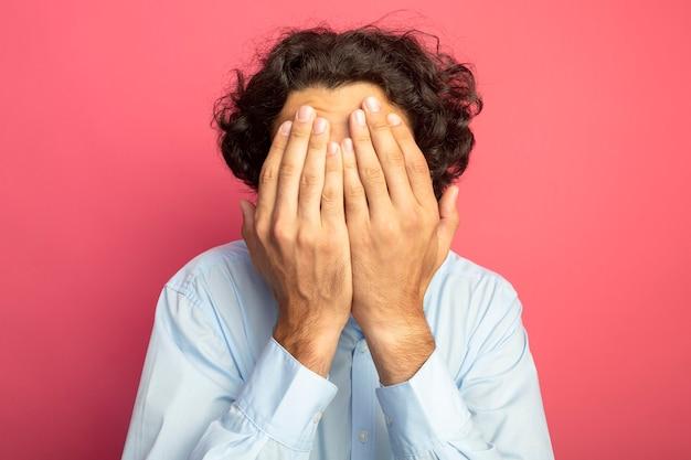 진홍색 벽에 고립 된 손으로 눈을 덮고 안경을 쓰고 젊은 잘 생긴 백인 남자의 근접 촬영보기