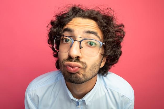 真っ赤な壁に分離されたキスジェスチャーをしている眼鏡をかけている若いハンサムな白人男性の拡大図