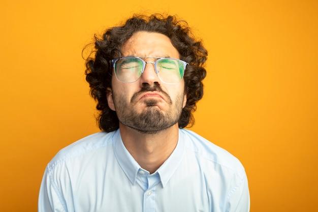 주황색 배경에 고립 된 안경을 쓰고 젊은 잘 생긴 백인 남자의 근접 촬영보기