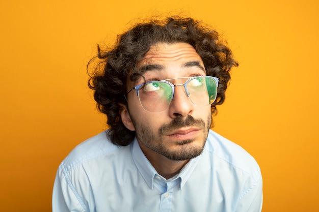 オレンジ色の壁に隔離の眼鏡をかけている若いハンサムな男のクローズアップ