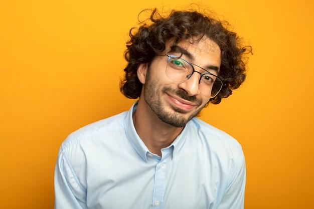 오렌지 벽에 고립 된 전면을보고 안경을 쓰고 젊은 잘 생긴 남자의 근접 촬영보기