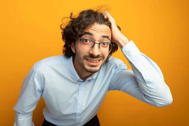 Крупным планом вид молодого красивого человека в очках, смотрящего на фронт, изолированного на оранжевой стене