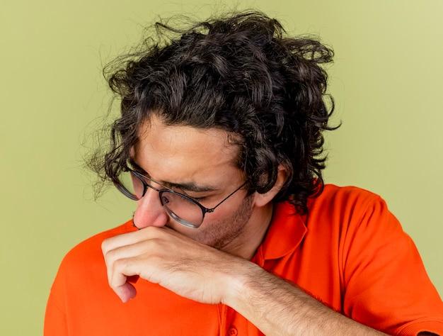 Крупным планом вид молодого больного человека в очках, вытирающего нос рукой с закрытыми глазами, изолированного на оливково-зеленой стене