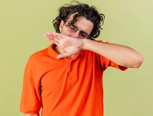 オリーブグリーンの壁に隔離された目を閉じて手で鼻を拭く眼鏡をかけている若い病気の男の拡大図