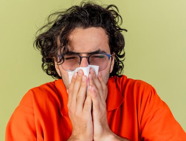 Крупным планом вид молодого больного человека в очках, вытирающего нос салфеткой с закрытыми глазами, изолированного на оливково-зеленой стене