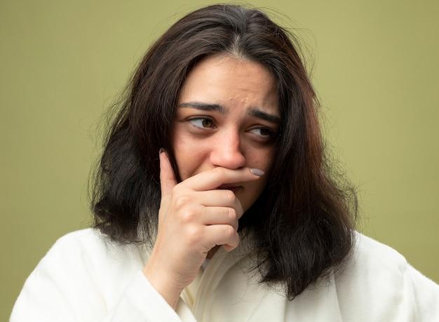 オリーブグリーンの壁に分離されたローブを着ている若い病気の女性の拡大図