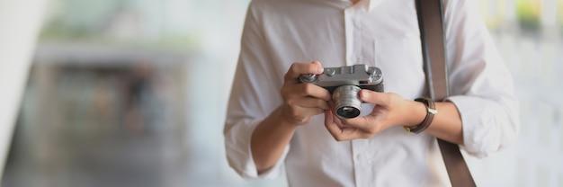 デジタルカメラで彼の写真をチェックする若い男性カメラマンのクローズアップ表示