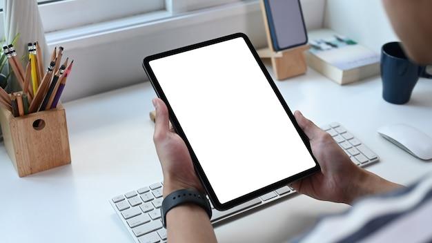 Крупным планом вид молодого человека-фрилансера, держащего цифровой планшет с пустым экраном в домашнем офисе