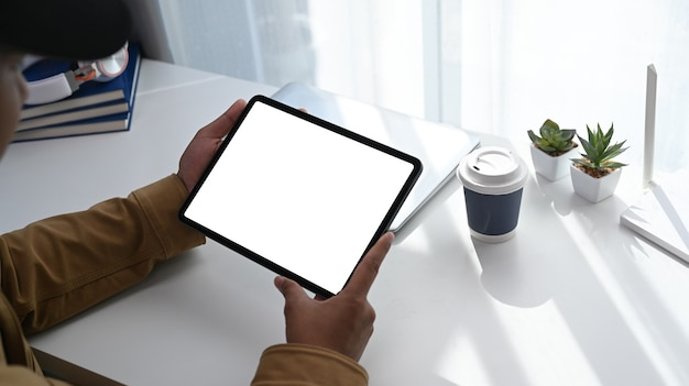 Крупным планом вид рук молодого человека с помощью цифрового планшета на его рабочем месте возле окна с солнечной вспышкой.