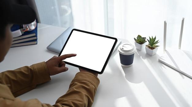 Крупным планом вид молодого человека, использующего цифровой планшет во время работы в интернете дома.