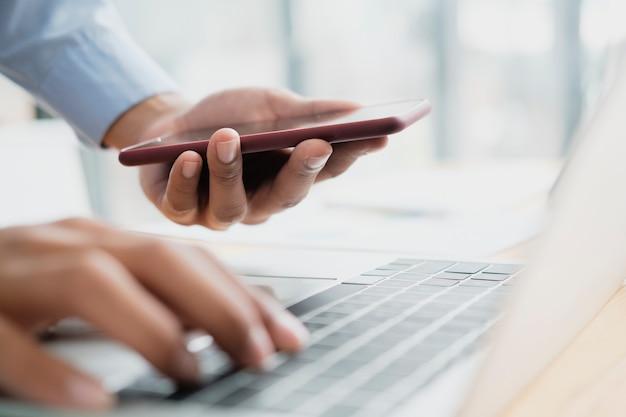 スマートフォンを使用して若いプロのビジネスマンのクローズアップビューは、コンピューターのラップトップに接続します