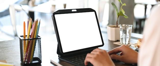 디지털 태블릿의 키보드에 입력하는 젊은 여성 디자이너의보기를 닫습니다