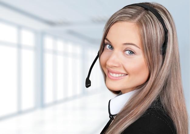 ヘッドフォン、コールセンター、またはサポートの概念を持つ若い女性の顔のクローズアップビュー