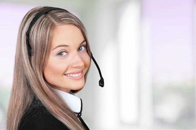 Крупным планом лицо молодой женщины с наушниками, колл-центр или концепция поддержки