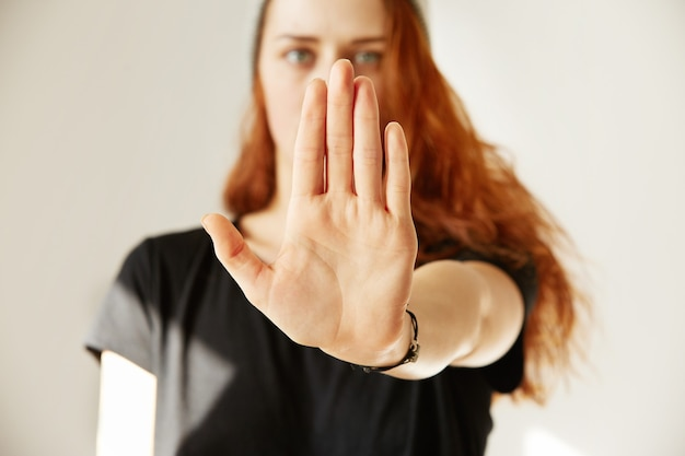 彼女の手で停止ジェスチャーを作る若い女性のクローズアップ表示