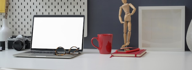 Close up view of office desk with mock-up laptop, decorations and office supplies