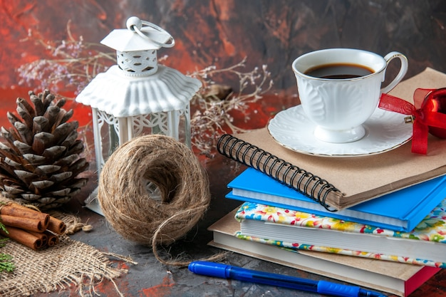 Close up view of office suppliances and pen cinnamon limes conifer cone and a cup of tea a ball of rope on dark background