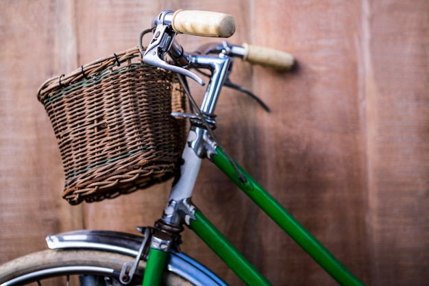 Close up view of a old green bike against a wooden wall