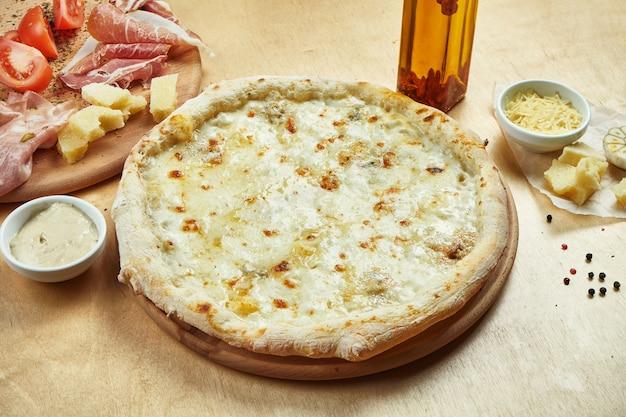 Закройте вверх по взгляду на аппетитной пицце 4 сыров с грушей на деревянном столе в ресторане. итальянская кухня.