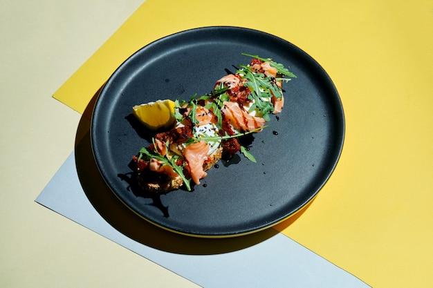 ルッコラとライ麦パンの食欲をそそるトーストのクローズアップビュー、半熟卵、サーモン、色付きの表面の黒い皿に天日干しトマト朝食用食品