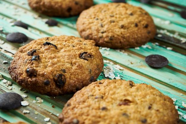 緑の木製のテーブルにチョコレートと焼きたてのクッキーのビューを閉じます。紅茶やコーヒーに美味しいデザート。レシピの写真。セレクティブフォーカス