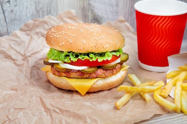 Крупным планом вид на гамбургер с картофелем на коричневой бумаге ремесло. традиционное фаст-фуд. свежий вкусный чизбургер с листьями салата, помидорами, сыром и огурцом. скопируйте пространство для дизайна. нездоровая пища. жир