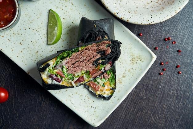 Закройте вверх по взгляду на буррито с говядиной, рисом, томатами, мозолью и болгарским перцем в черном пита на коричневой плите с томатной сальсой и гуакамоле. вегетарианский рулет с шаурмой