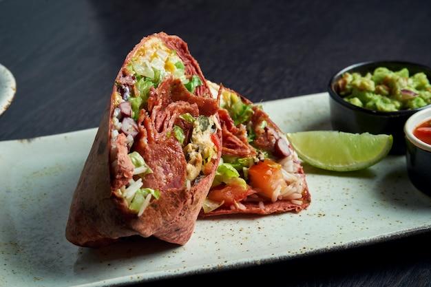 Закройте вверх по взгляду на буррито с чоризо салями, рисом, томатами, мозолью и болгарским перцем в коричневом пита на коричневой плите с сальсой томата и гуакамоле. вегетарианский рулет с шаурмой